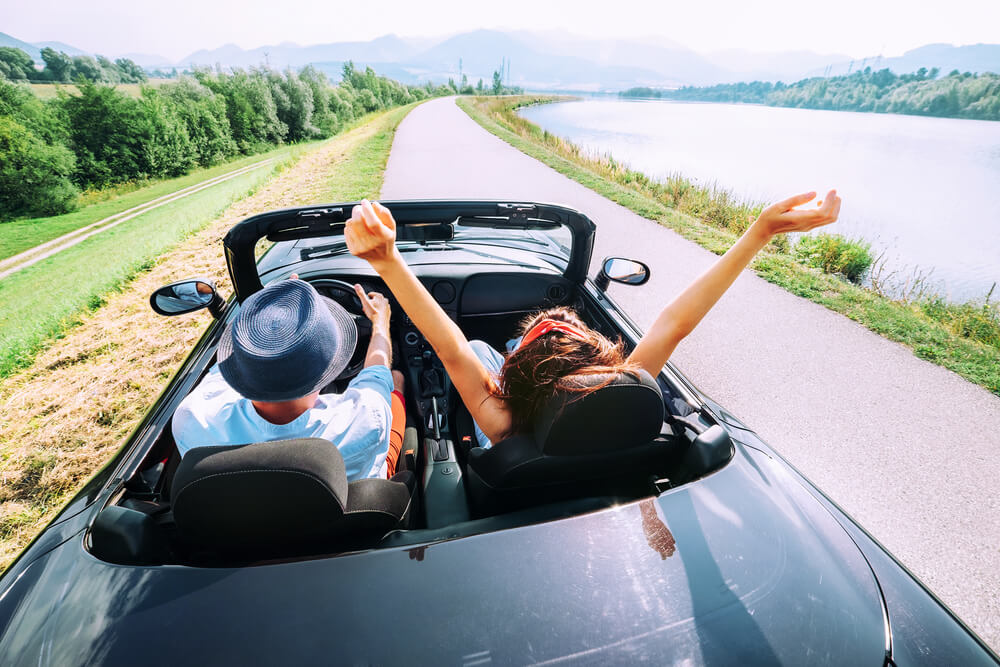 A man is taking his girlfriend for a ride in a convertible